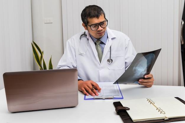 Médico diagnosticar e analisar no filme de raio-x do paciente Foto Premium