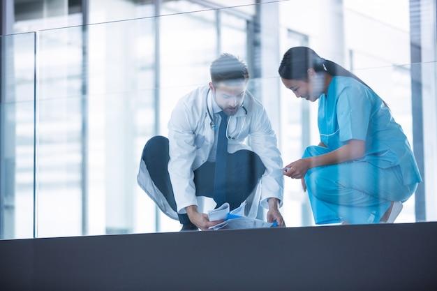 Médico e enfermeira coletando relatórios médicos caídos do chão Foto Premium