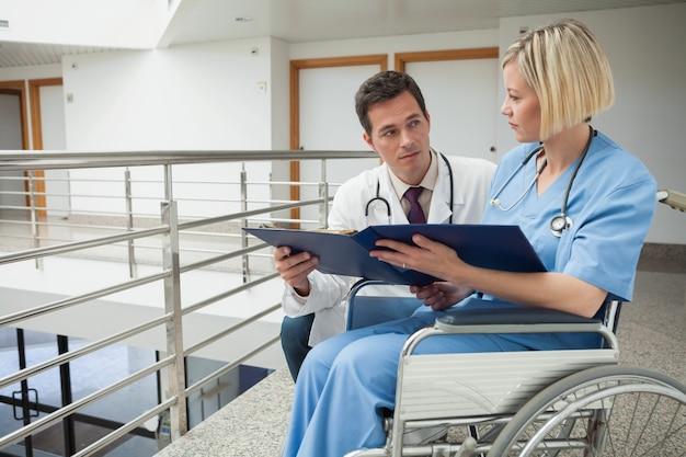 Médico e enfermeira em cadeira de rodas, estudando pasta Foto Premium