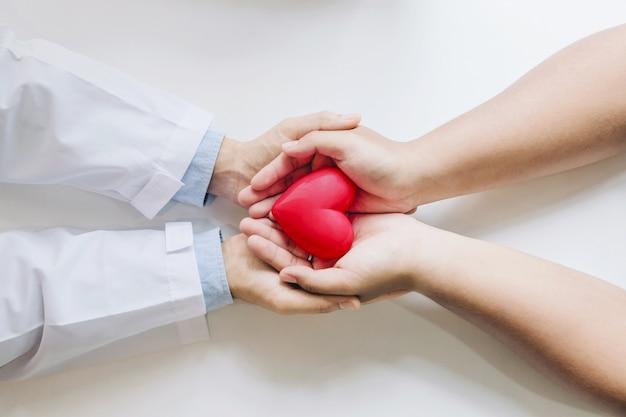Médico e o paciente segurando um coração vermelho juntos. Foto Premium