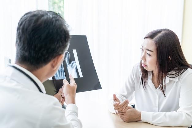 Médico e paciente do sexo feminino asiático estão discutindo Foto Premium