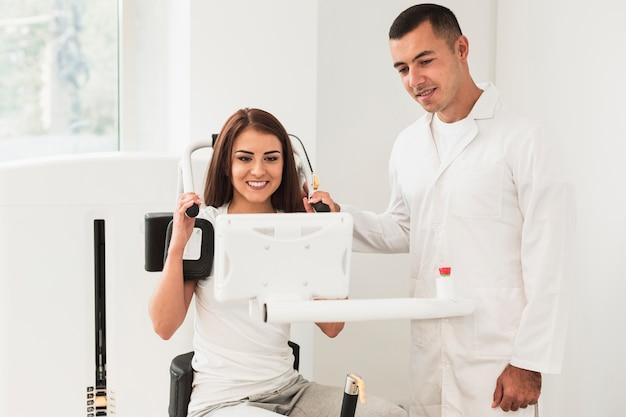 Médico e paciente do sexo feminino assistindo uma tela Foto gratuita
