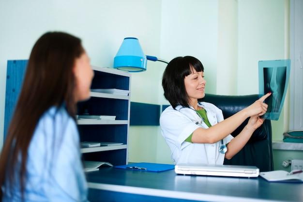 Médico e paciente olhando para um raio-x Foto gratuita