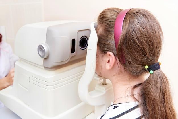 Médico examina os olhos da criança com ceratômetro Foto Premium