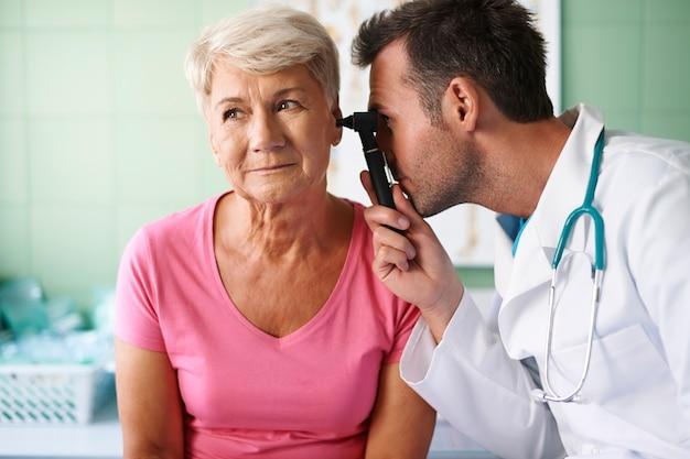 Médico examinando a orelha de uma mulher idosa Foto gratuita