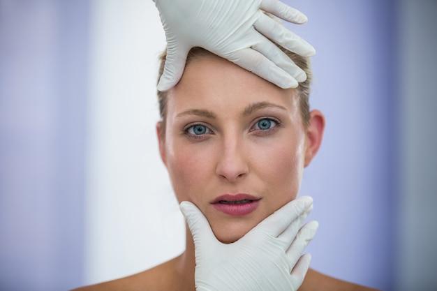 Médico examinar pacientes do sexo feminino rosto de tratamento cosmético Foto gratuita