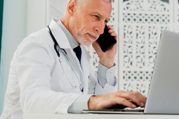 Médico falando no telefone e usando o laptop Foto gratuita