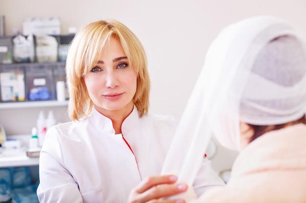 Médico faz um curativo na cabeça do paciente na clínica Foto Premium