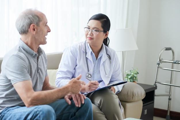 Médico feminino asiático falando com paciente caucasiano sênior durante chamada de casa Foto gratuita