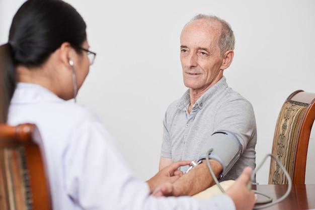 Médico feminino asiático tomando pressão de sangue do paciente do sexo masculino caucasiano sênior Foto gratuita