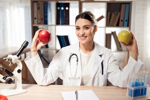 Médico feminino está segurando duas maçãs nas mãos. Foto Premium