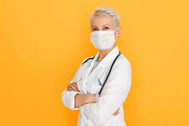 Médico feminino maduro confiante posando contra o fundo da parede amarela em branco, vestindo bata branca médica e máscara cirúrgica protetora, cruzando os braços sobre o peito. vírus, infecções e bactérias Foto gratuita