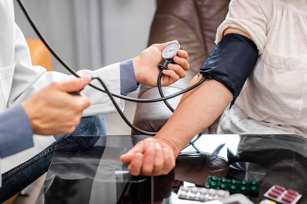 Médico homem mãos medir tensão para um paciente Foto gratuita