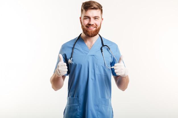 Médico homem sorridente, mostrando os polegares para cima gesto com as duas mãos Foto gratuita