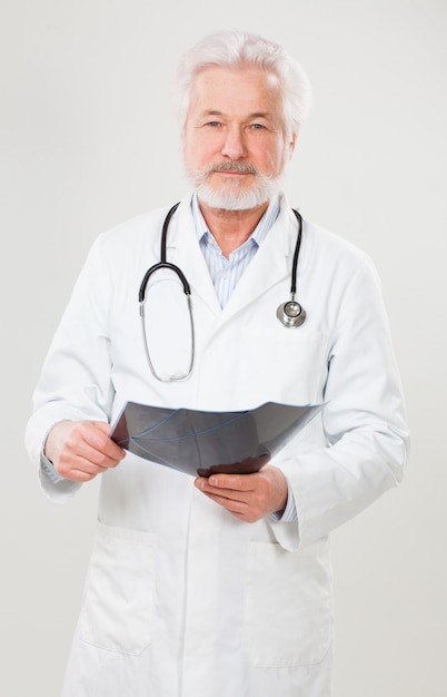 Médico idoso bonito com radiografia Foto gratuita
