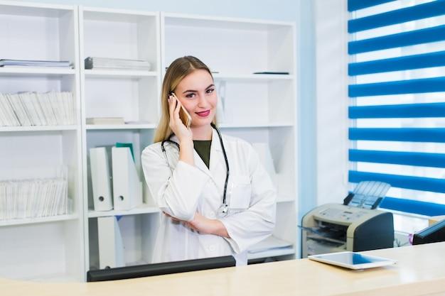 Médico jovem bonita falando no telefone Foto Premium