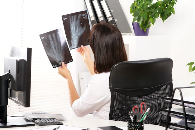 Médico jovem está olhando xray Foto gratuita