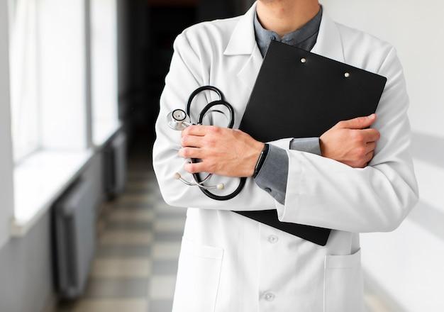 Médico mãos segurando uma prancheta e estetoscópio Foto gratuita