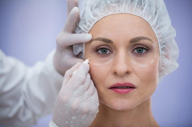 Médico marcando pacientes do sexo feminino para tratamento cosmético Foto gratuita