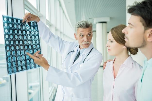 Médico masculino experiente, mostrando seus pacientes resultados de raios-x. Foto Premium