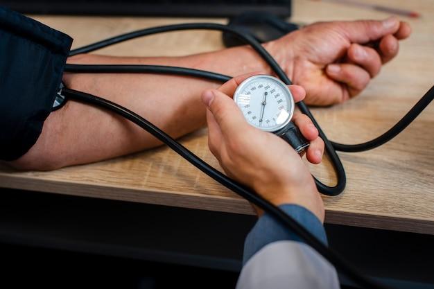 Médico masculino mão medir tensão Foto gratuita