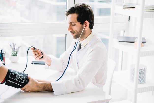 Médico masculino, medindo pressão sangue, de, paciente, em, clínica Foto gratuita
