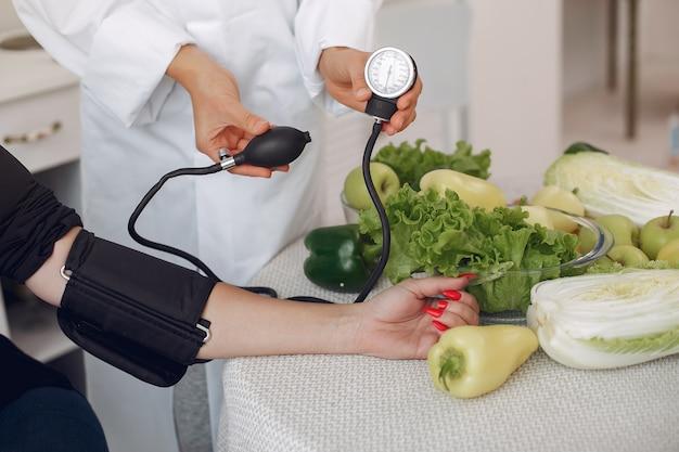 Médico mede a pressão do paciente na cozinha Foto gratuita
