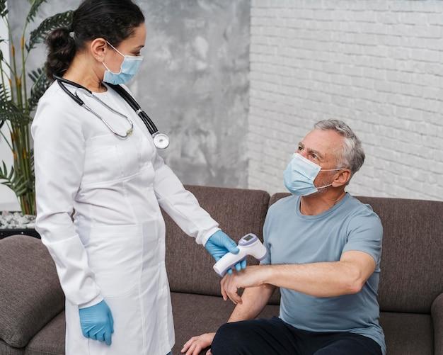 Médico medindo a temperatura do paciente Foto gratuita