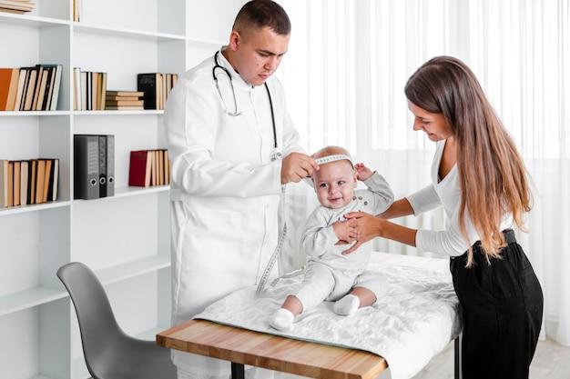 Médico medir a cabeça do bebê recém-nascido Foto gratuita