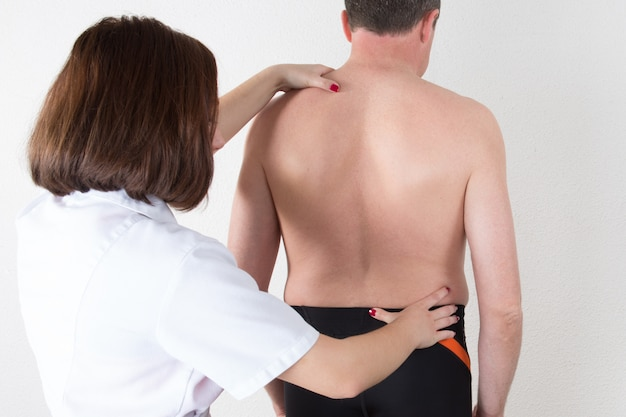 Médico mulher fisioterapeuta examinando as costas do paciente Foto Premium