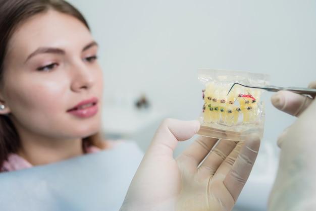 Médico ortodontista explica ao paciente como os aparelhos são dispostos Foto Premium