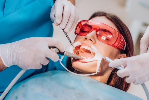 Médico ortodontista realiza um procedimento para limpeza dos dentes Foto Premium