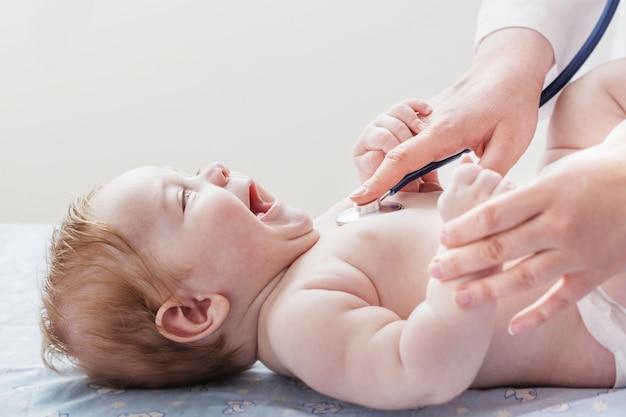 Médico ouve criança pequena com estetoscópio Foto Premium