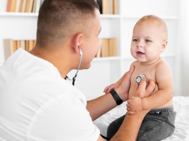 Médico ouvir bebê pequeno com estetoscópio Foto gratuita