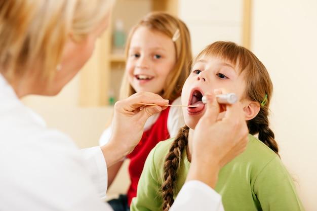 Médico pediatra examinar a garganta da menina Foto Premium