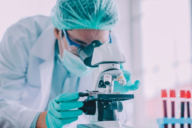 Médico pesquisa vacina vírus corona, médico analisando microscópio no hospital de laboratório Foto Premium