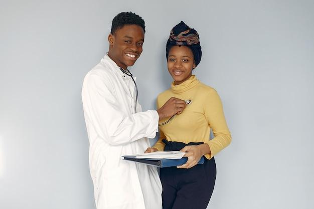Médico preto em um uniforme branco com um estetoscópio Foto gratuita