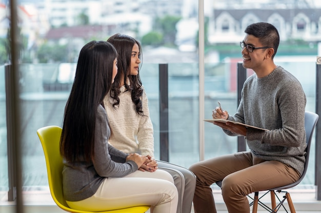 Médico psicólogo profissional masculino asiático, dando a consulta aos pacientes lésbicas amantes Foto Premium