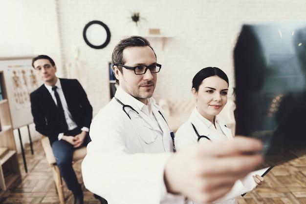 Médico qualificado com estetoscópio e enfermeira examinando o raio-x. Foto Premium