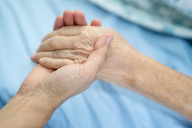 Médico segurando mãos comoventes, paciente idosa ou idosa asiática com amor Foto Premium