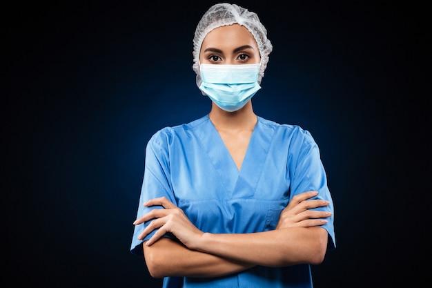 Médico sério em máscara médica e boné olhando Foto gratuita