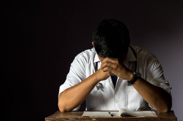 Médico sério estava estressado no quarto escuro. Foto Premium
