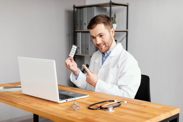 Médico sorridente de tiro médio na mesa Foto gratuita