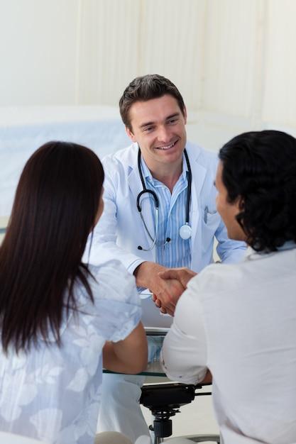 Médico sorridente que explica o diagnóstico para um casal Foto Premium