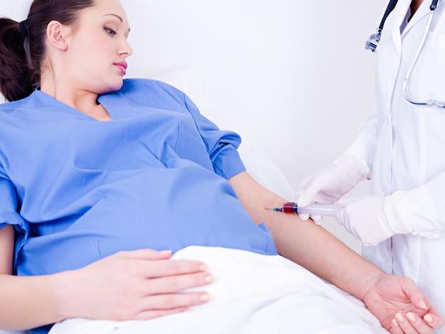 Médico tira sangue na análise de uma veia da gestante Foto gratuita