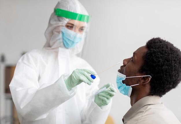 Médico tirando amostra de teste de coronavírus Foto gratuita