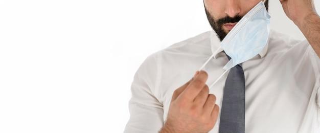 Médico tirando sua máscara médica com espaço de cópia Foto gratuita