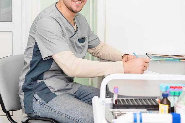 Médico trabalhando, escrevendo na papelada Foto Premium