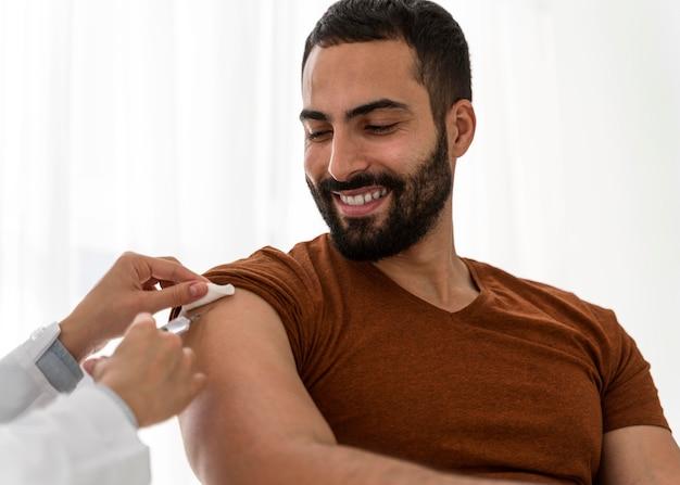Médico vacinando um homem bonito e sorridente Foto gratuita