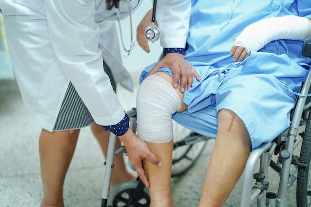 Médico verifica o joelho com bandagem na cadeira de rodas Foto Premium